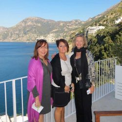 Lynn Cicarelli and two friends on a white balcony on the Amalfi Coast