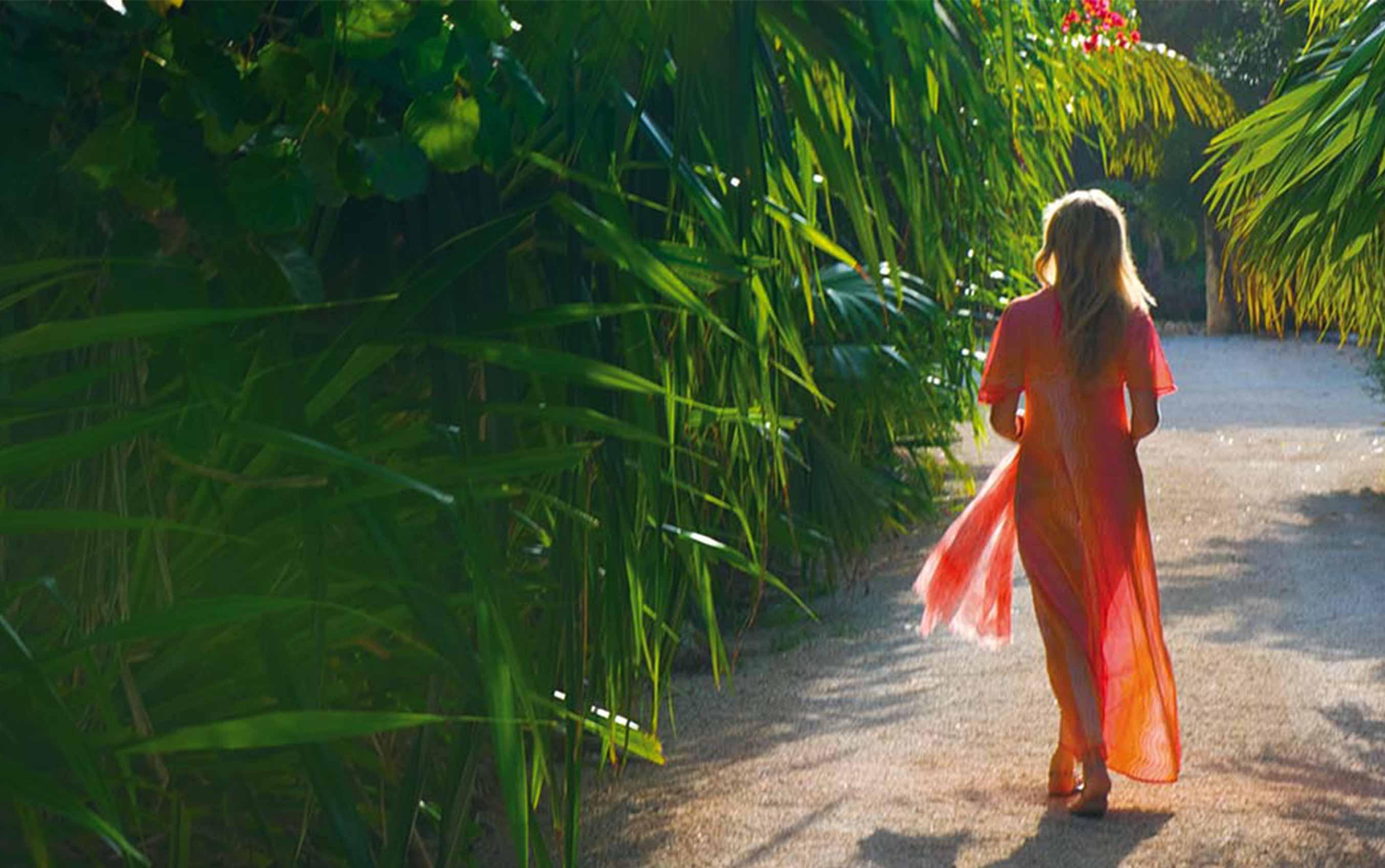 blonde woman walking on a path cutting through tropical foliage